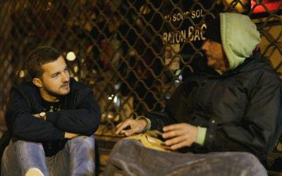 deux hommes assis par terre et qui discutent