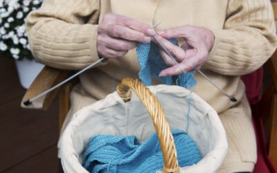 Closeup Of Older Woman Sitting And Knitting